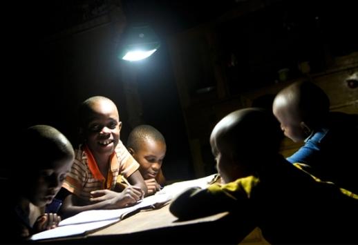 Trẻ em Uganda tập đọc dưới ánh đèn điện mặt trời (Ảnh: Solar Sisters)