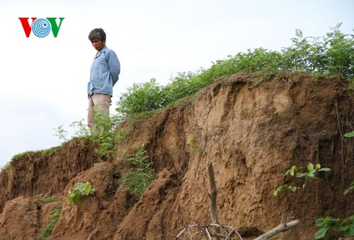 Một người dân đứng bên bờ sông bọ lở do hút cát làm ảnh hưởng đến dòng chảy (Ảnh: VOV Online)