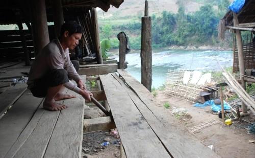 Hoàng Văn Bun tự tay dỡ ngôi nhà mình, phía dưới là dòng Nậm Mu xanh thẫm (Ảnh: nongnghiep.vn)