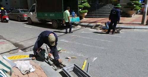 Công nhân đang lắp đặt nắp cống (Ảnh: BizLIVE.vn)
