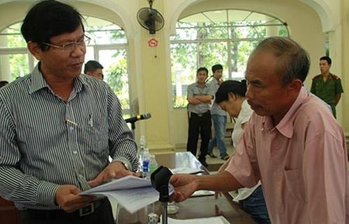 Ông Võ Văn Thương, Chánh Văn phòng UBND TP Đà Nẵng (trước đây là chủ tịch UBND quận Cẩm Lệ), trao đổi với hộ ông Trần Quang Anh (tổ 21, giáo xứ Cồn Dầu). Ảnh: LÊ PHI