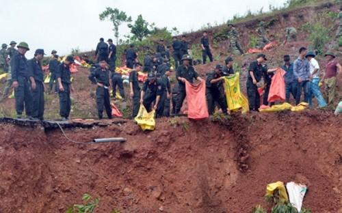 Hàng trăm chiến sĩ bộ đội, biên phòng và công an cùng người dân khắc phục sự cố vỡ đập (Ảnh: Dân Việt)