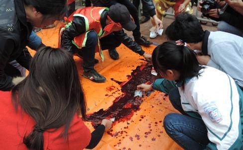 Người dân dùng tiền lẻ quyệt máu lợn vừa bị chém để lấy may. (Ảnh: Pháp luật Việt Nam)
