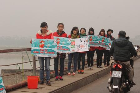 Các tình nguyện viện giơ biển tuyên truyền cho người dân tại cầu. (Ảnh: Thu Trang)