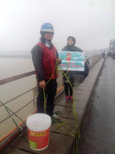 Mặc cho thời tiết giá rét mưa phùn, các bạn sinh viên tình nguyện vẫn đứng ở cầu Long Biên hướng dẫn, giúp đỡ người dân thả cá chép mà không thả túi nilon xuống sông và gom rác tại cầu. (Ảnh: Nguyễn Hưởng)