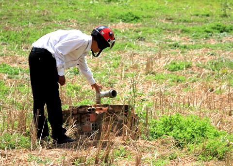 Anh Tâm dùng giếng khoan bơm nước ra ao tạm để tưới cho khoai môn. (Ảnh: Đại Đoàn Kết)