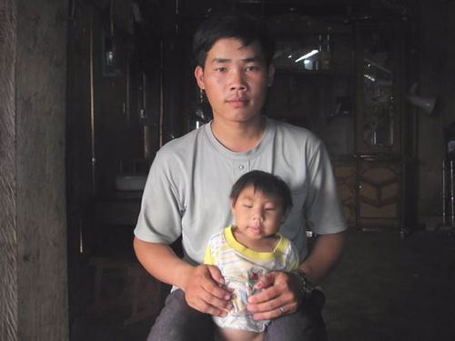 Trưởng thôn Giàng A Nù bên đứa con tật nguyền. (Ảnh: Công an TP Đà Nẵng)
