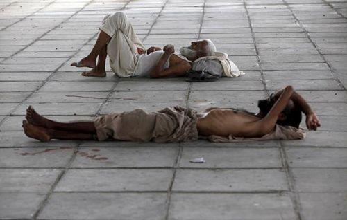 Hai người đàn ông ngủ dưới bóng râm của một cây cầu trong thời tiết nắng nóng dữ dội ở Karachi, Pakistan vào ngày 22/6/2015. (Ảnh: REUTERS / Akhtar SOOMRO)