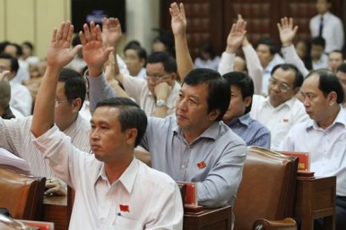Các đại biểu biểu quyết thông qua tờ trình của UBND TP HCM về tăng phí ô tô (Ảnh: Hoàng Triều/nld.com.vn)