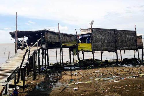 """Sau khi bị biển """"lấy mất"""" căn nhà, anh Nguyễn Văn Nghề dựng tạm căn chòi cùng 5 người trong gia đình sống chơ vơ phía biển (Ảnh: Nhật Hồ)"""