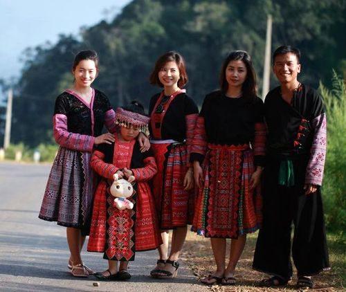 Tráng A Chu làm hướng dẫn viên cho đoàn khách du lịch. Những bộ váy người H'mong do chính tay vợ A Chu dệt được khách du lịch rất yêu thích (Ảnh: Ngọc Lâm)
