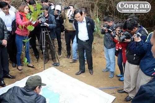 Ông Phùng Tấn Viết nghe cán bộ kiểm lâm báo cáo, xác định khu vực rừng bị xâm hại trên bản đồ.