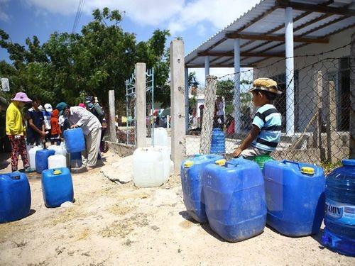 Người dân tại Ninh Thuận nhận nước từ đoàn hỗ trợ (Ảnh: Minh Quyết/TTXVN)