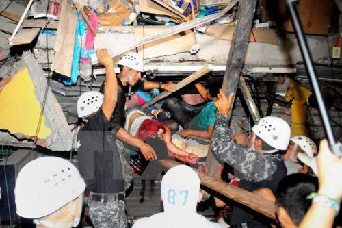 Lực lượng cứu hộ giải cứu người còn sống bị mắc kẹt trong một căn nhà đổ nát sau trận động đất ở Manta (Ảnh: AFP/TTXVN)
