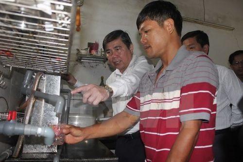 Chủ tịch UBND Thành phố Hồ Chí Minh Nguyễn Thành Phong kiểm tra việc thực hiện cung cấp nước sạch bằng thiết bị lọc nước tại hộ gia đình ông Lê Vũ Hồng ở ấp Bến Mương, xã An Nhơn Tây (Ảnh: Thanh Vũ/TTXVN)