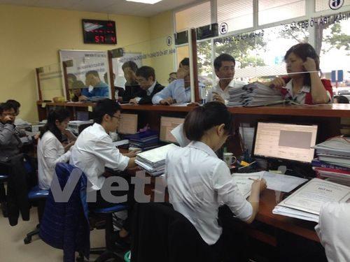 Người dân đi làm thủ tục cấp sổ đỏ tại Văn phòng đăng ký đất đai (Ảnh: H.T/Vietnam+)