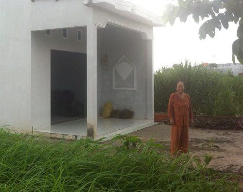 Bà Tím 60 tuổi, trước căn nhà trống trơn ở khu tái định cư đầy cỏ dại