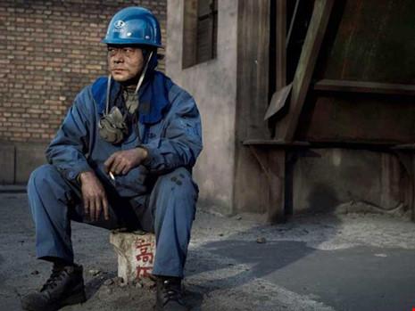 """Một công nhân của một doanh nghiệp thép đang trầm ngâm vì DN ô nhiễm phải """"tái định cư"""" tại các nước nghèo hơn. Ảnh: AFP"""