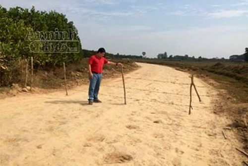 """Sáng 6-12, khi phóng viên trở lại hiện trường thì các đối tượng khai thác trộm đất """"mượn"""" của Trung đoàn 921 đã rào độc đạo này lại bằng cọc gỗ và dây thép gai"""